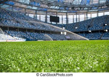 Grass on stadium in sunlight. Closeup of a green football field. Wet stadium grass in the morning light during watering irrigation. Close up macro of soccer or football field. green grass field background. Empty stadium