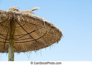 Grass parasol on a blue sky