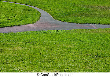 Three intersecting paths through a green field of grass.
