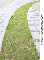 Grass path curve between cement block.