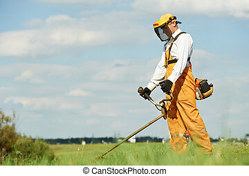 Grass trimmer works - Young worker with power tool string...