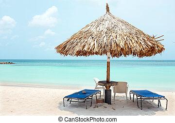 Grass umbrella at the beach on Aruba island at sunset