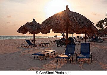 Grass umbrellas at the beach on Aruba island at sunset
