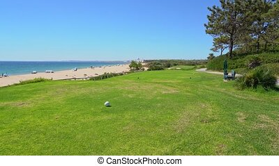 Grassy field near a pleasant looking beach and glistering ocean water in Vale do Lobo, Portugal. High quality 4k footage