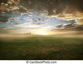 Beautiful sunset with dramatic clouds over grassy field