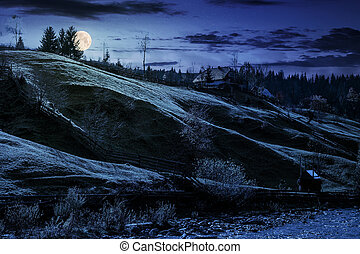 grassy rural hillside near the village at night in full moon...