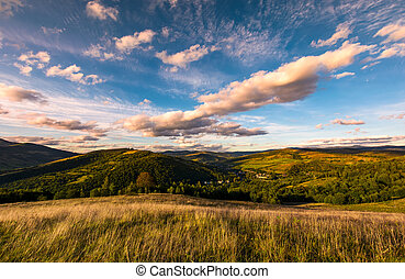 grassy slope in mountainous countryside at sunset. beautiful...