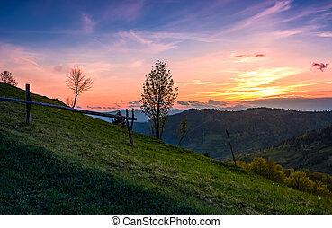 grassy slope rural area at sunset. beautiful mountainous...