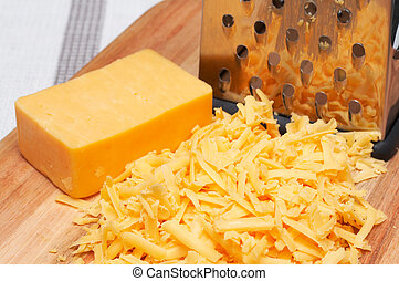 Grated cheddar cheese on wooden board with grater next to it