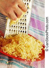 grated yellow cheese with a metal grater closeup