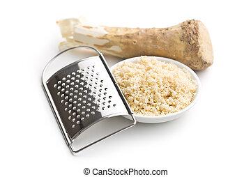 grated horseradish root on white background
