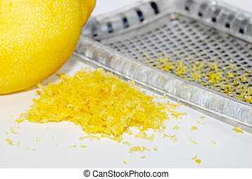 Small heap of grated lemon zest with a whole lemon and grater