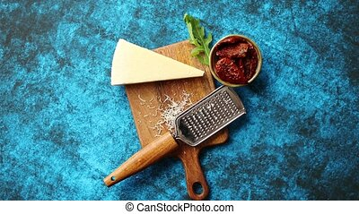 Grated parmesan cheese and metal classic grater placed on...