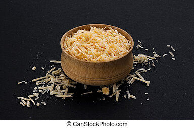 Grated parmesan cheese on black background