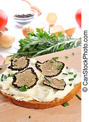 grated summer truffle with soft cheese on a slice of bread