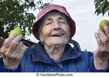 smiling grateful senior woman with two fig fruits