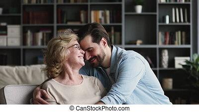 Grateful loving adult son embracing mature mum at home - ...