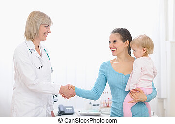 Grateful mom shaking hand to middle age pediatric doctor
