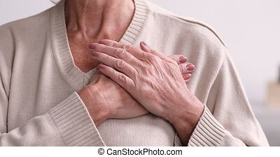 Grateful pleased senior woman holding hands on chest, ...