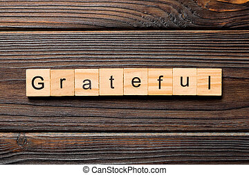 Grateful word written on wood block. Grateful text on table, concept