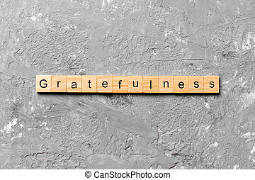 gratefulness word written on wood block. gratefulness text on cement table for your desing, concept
