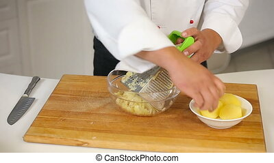 Grating boiled potatoes for potatoe pancakes dough