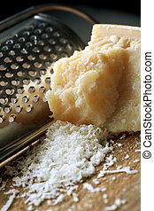 Grating Parmesan Cheese - Parmesan cheese with a grater. ...
