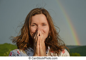 Beautiful young woman looking thanking sun has returned