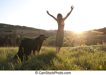 Beautiful young woman raises her arms to the sun whilst walking her dog