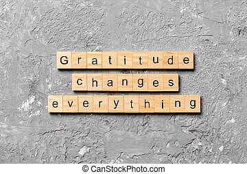 Gratitude changes everything word written on wood block. Gratitude changes everything text on cement table for your desing, concept