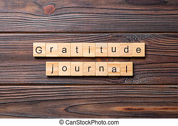 Gratitude Journal word written on wood block. Gratitude Journal text on cement table for your desing, concept