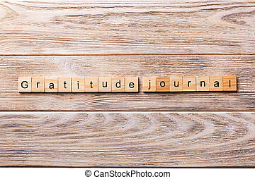 Gratitude Journal word written on wood block. Gratitude Journal text on wooden table for your desing, concept