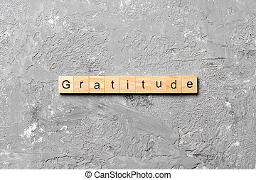 gratitude word written on wood block. gratitude text on cement table for your desing, concept