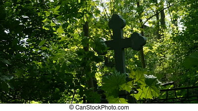 Grave cross among the lush greenery of the cemetery