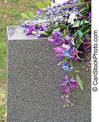 silk flowers on a cemetery grave tombstone