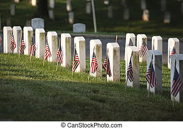 Grave markers with flags at Arlington National Cemetery on...