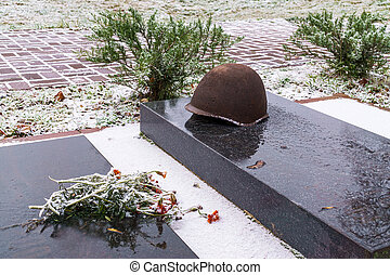 Gray granite slab and rusty military helmet on grave of unknown soldier. Winter day