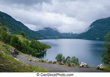 Gravel road at norwegian beautiful fjord shore.