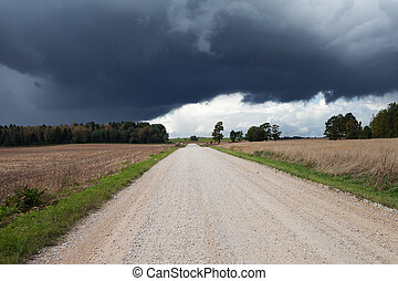 Gravel road under cloudy sky.