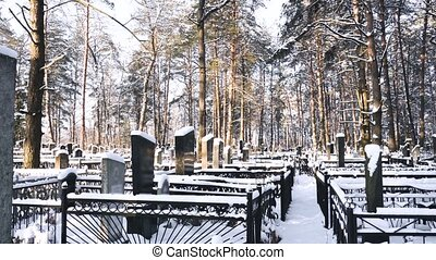 Graves at snowy Christian and Jewish cemetery or graveyard...
