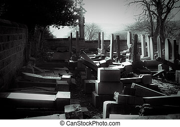 Old graveyard in ruins with toppled and broken head stones.