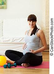 Gravid woman taking break from fitness exercises