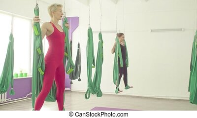 Steadicam shot. Gravity yoga. Two women in red and black suits doing exercises in hammocks
