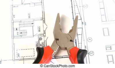 Gray and red pliers on building plan, scheme, rotation,...