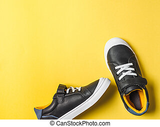 Gray and yellow sneakers on yellow background
