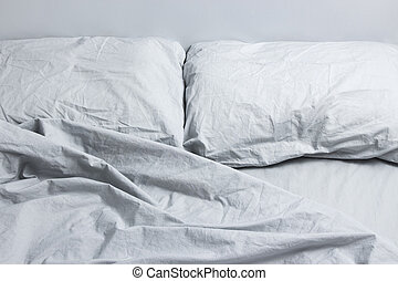 Gray bed linen - Messy bed with two pillows, gray bed linen.
