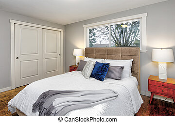 Gray bedroom interior with huge bed and tufted headboard.