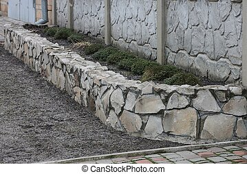 gray border of large stones and cobblestones outside on the ground with green ornamental plants
