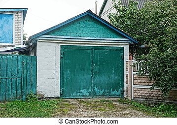 gray brick garage with a glazed green gate in the street