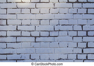 gray brick wall in white paint with gray cement under the rays the sun
